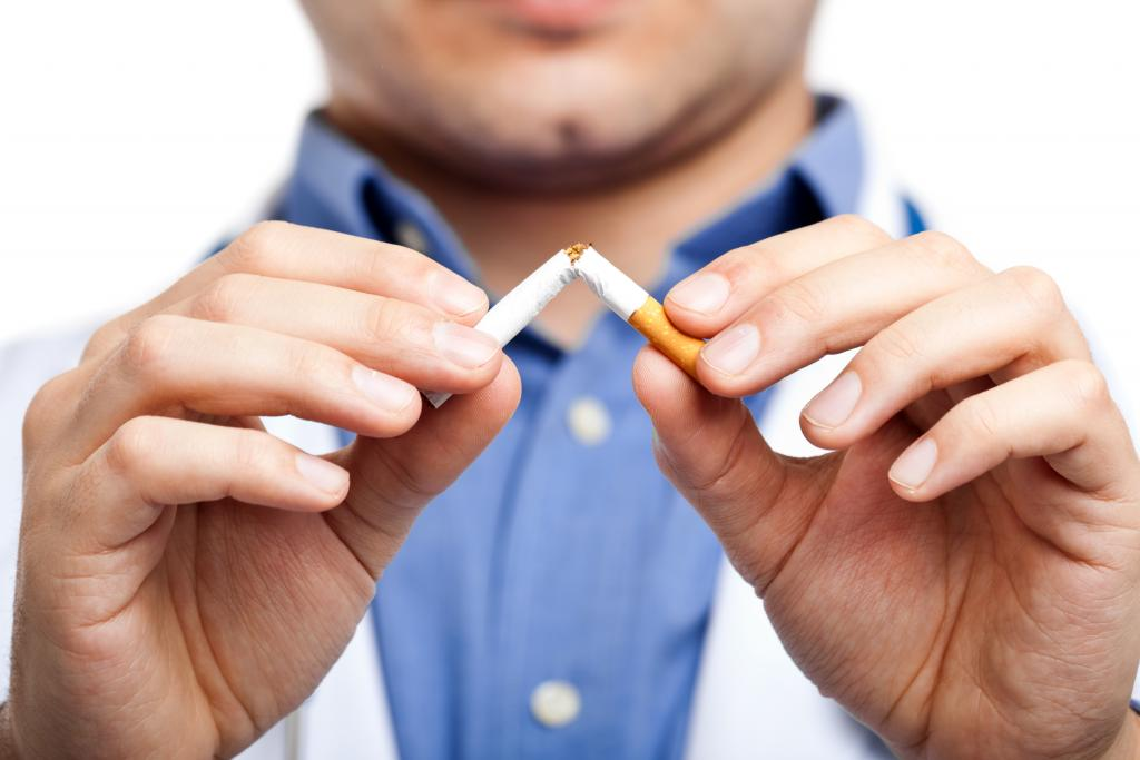 Человек ломает сигарету