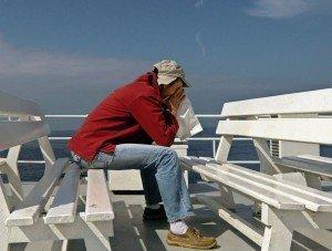 Человек сидит на судне с приступами морской болезни