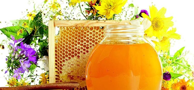 Мед в банке на фоне медовых сот и цветов