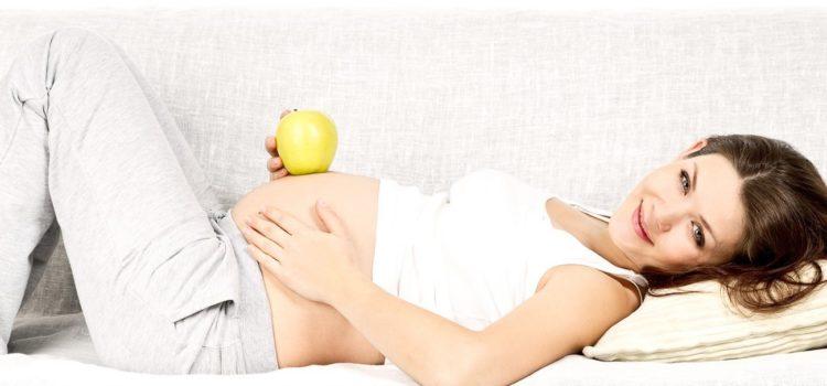 Беременная с яблоком лежит на диване