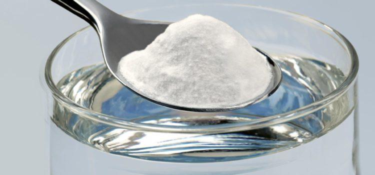 Сода в ложке над стаканом воды