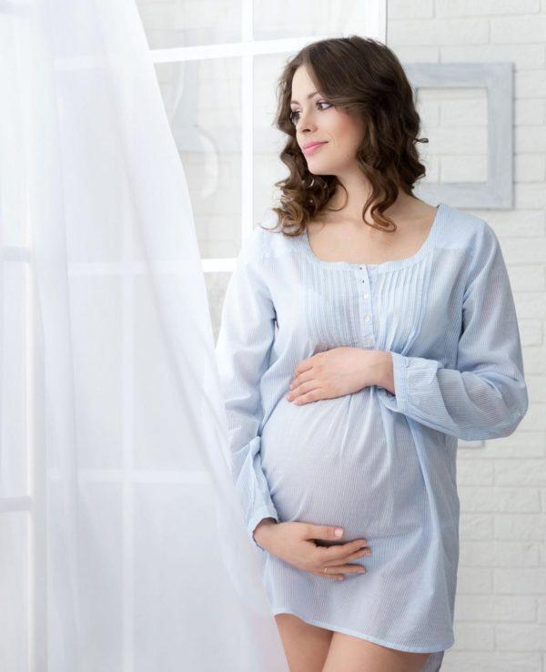 Беременная женщина у окна