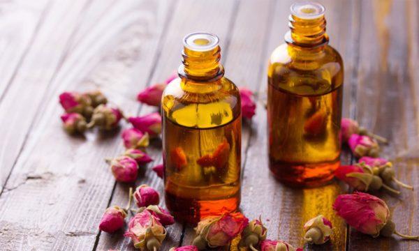 Розовые бутоны и масло во флаконах