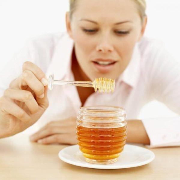 Девушка пробует мёд