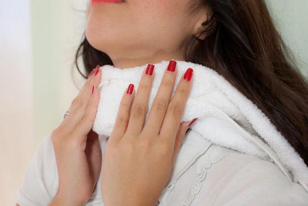 Девушка делает компресс на область щитовидной железы