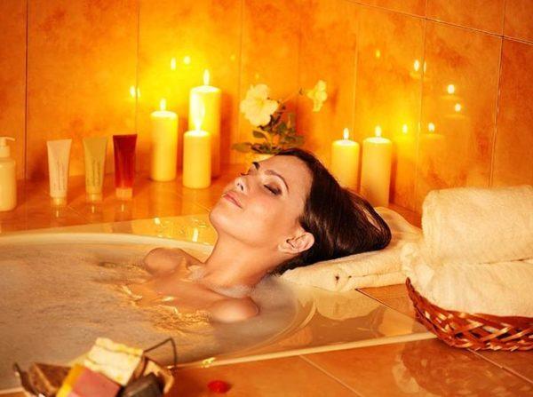 Девушка лежит в ванее при     свечах