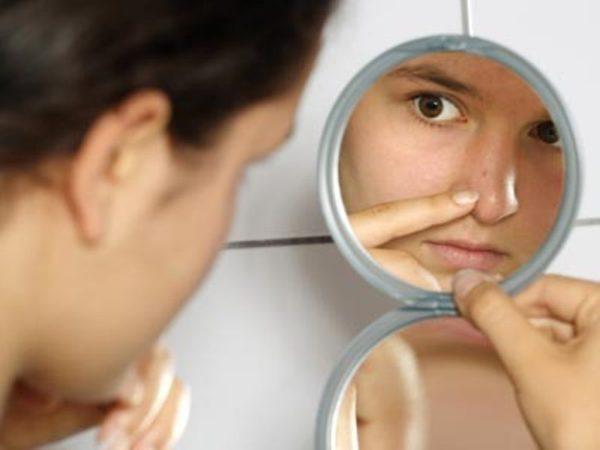 Девушка рассматривает лицо в зеркале