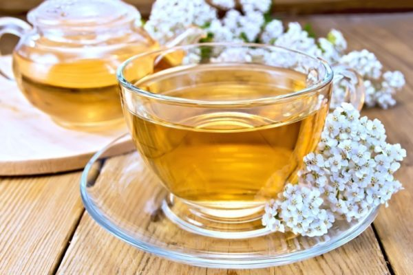 Чайник и прозрачная чашка с чаем и цветы тысячелистника