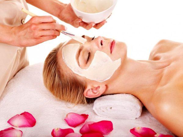 Маска с лепестками розы — косметолог кистью наносит её на лице девушки