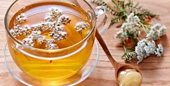 Стакан с чаем, цветы тысячелистника и ложечка мёда
