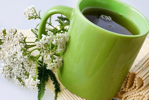 Зелёная чашка с чаем и цветы тысячелистника