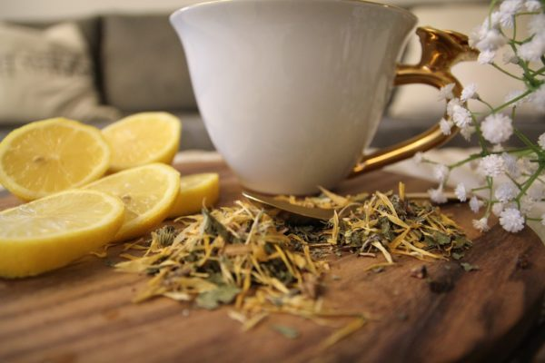 Белая чашка, лимон и сухие травы