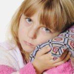 Ребёнок прикладывает солевой компресс к уху