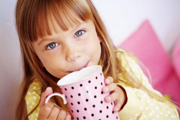 Девочка пьёт чай из большой кружки