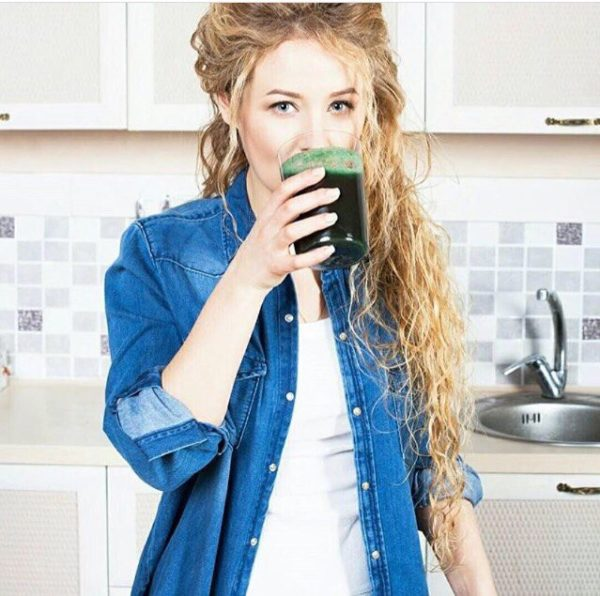 Девушка пьёт напиток из спирулины