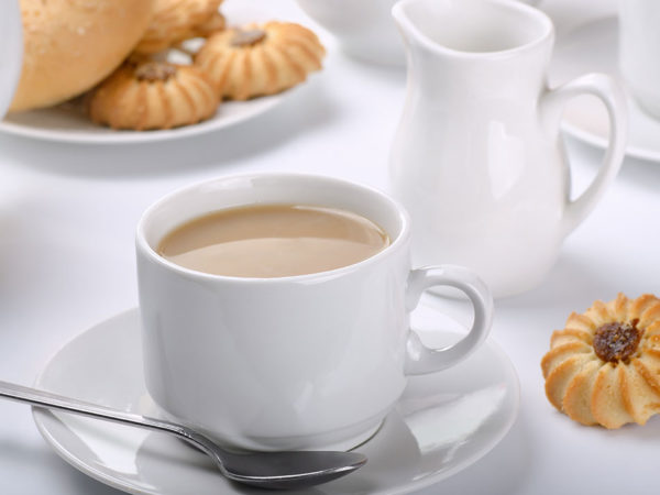 Чай с молоком в чашке на блюдце и молочник