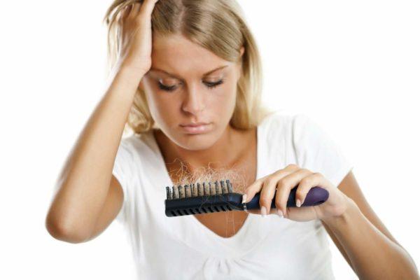 Девушка с грустью смотрит на выпавшие волосы