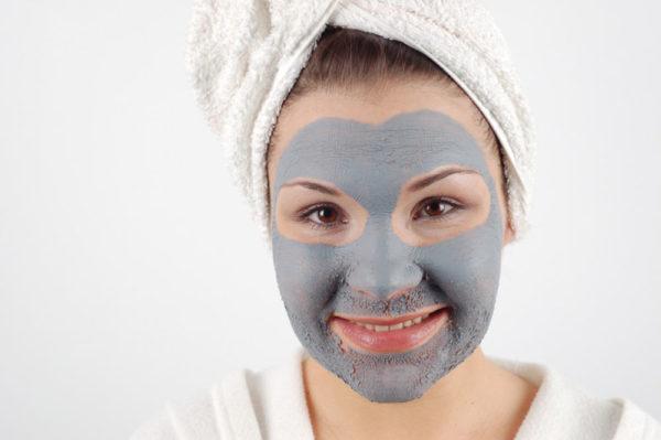 Глиняная маска на лице у девушки
