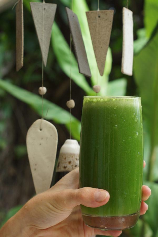 Стакан с зелёным соком в руке