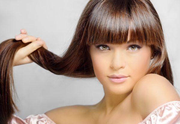Девушка держит прядь своих волос, показывая их красоту