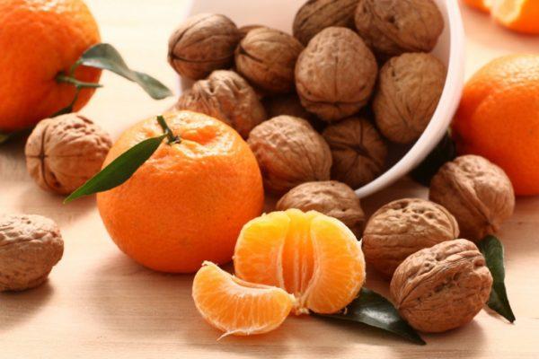 Мандарин, дольки мандарина, грецкие орехи на столе