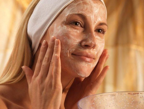 Симпатичная женщина накладывает маску из мандарина, мёда и сметаны
