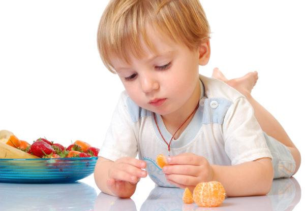 Ребенок трёх лет в белой футболке, лёжа на животе, держит в руках мандарин