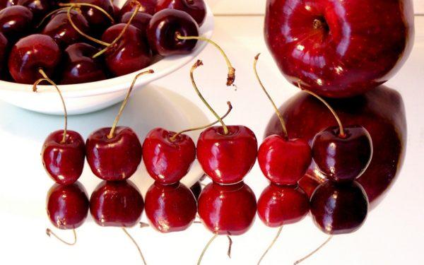 Собранные плоды вишни и яблоко